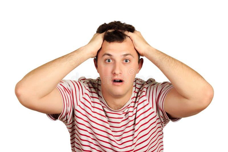 Shocked发昏了T恤杉的年轻人对负顶头用两只手 在白色背景隔绝的情感人 免版税图库摄影