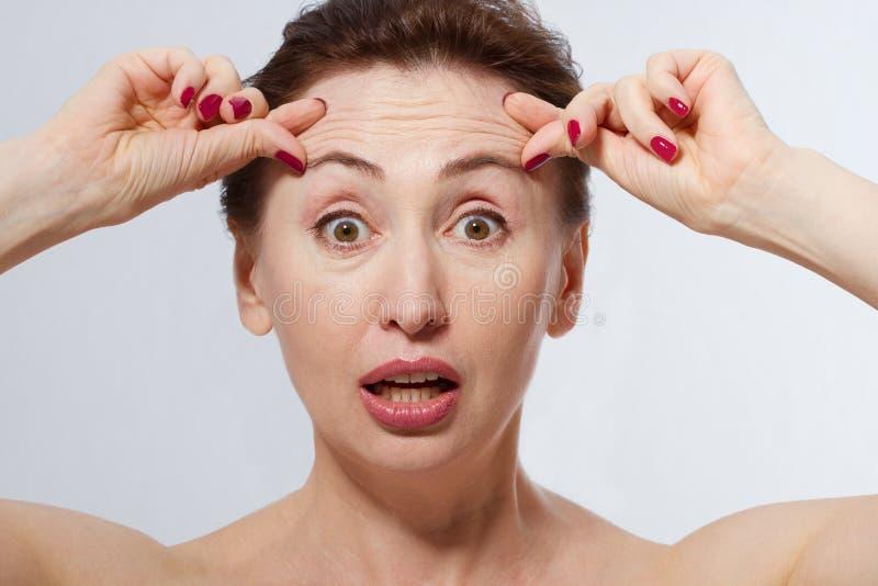 Shocked妇女画象有皱痕的在前额 胶原和面孔射入概念 更年期 播种的图象 复制Spac 免版税库存图片