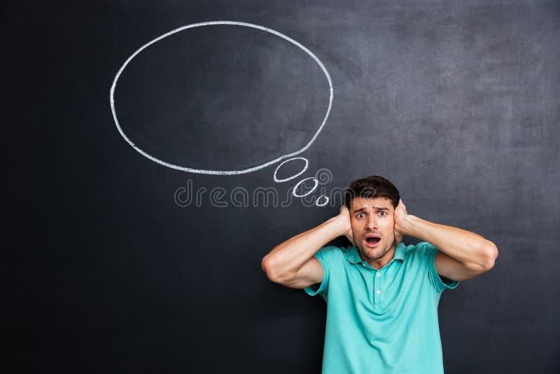 Shocked注重了人被盖的耳朵移交黑板背景 免版税库存图片