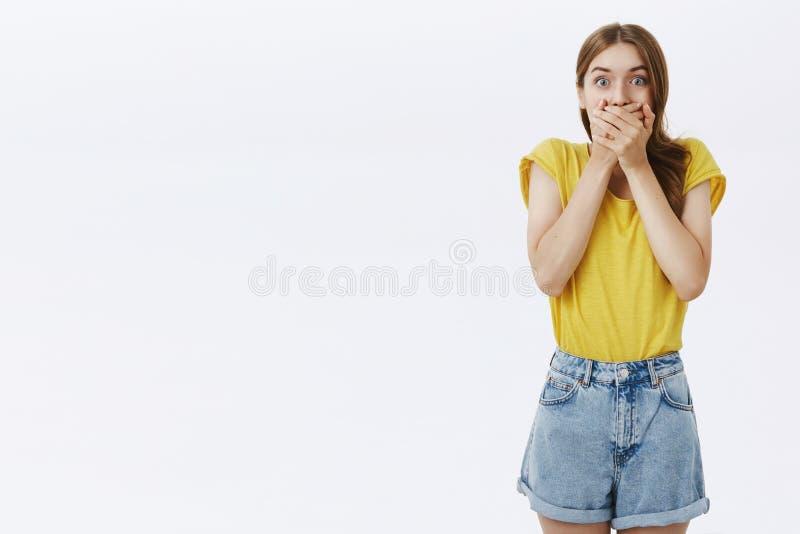 Shocked铭记了黄色T恤杉的可爱的白种人喘气女孩和的短裤盖从震动的嘴和 免版税库存照片