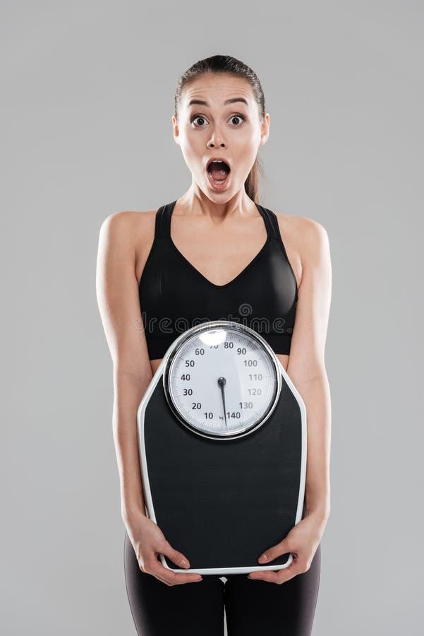 Shocked a étonné l'athlète de jeune femme tenant la balance image libre de droits