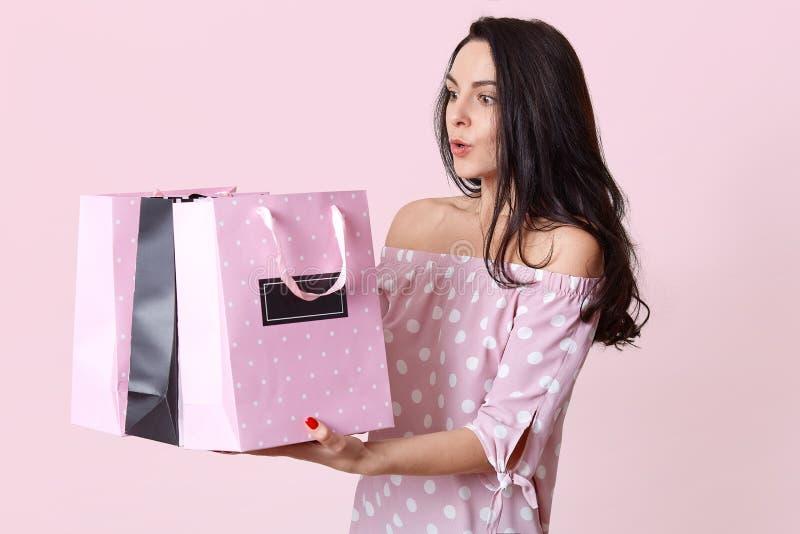 Shocked a étonné les sacs européens de prises de jeune femme, étonnés pour recevoir beaucoup de présents, habillés dans la robe d photo libre de droits