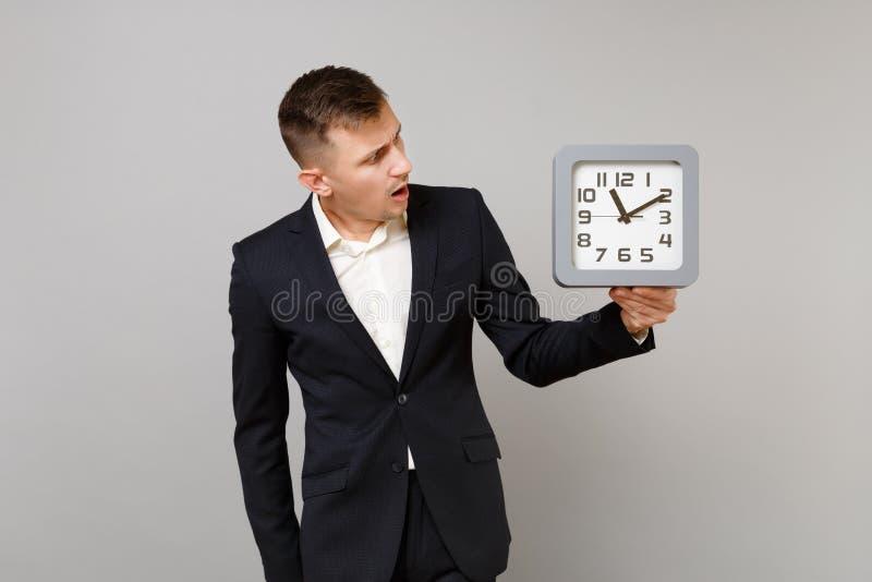 Shocked раздражал молодой бизнесмена в рубашке классического черного костюма белой смотря на квадратных часах в руке изолированно стоковая фотография