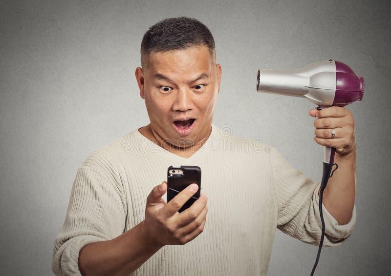 Shocked überraschte den Mann, der auf dem Smartphone schaut, der hairdryer hält lizenzfreie stockbilder