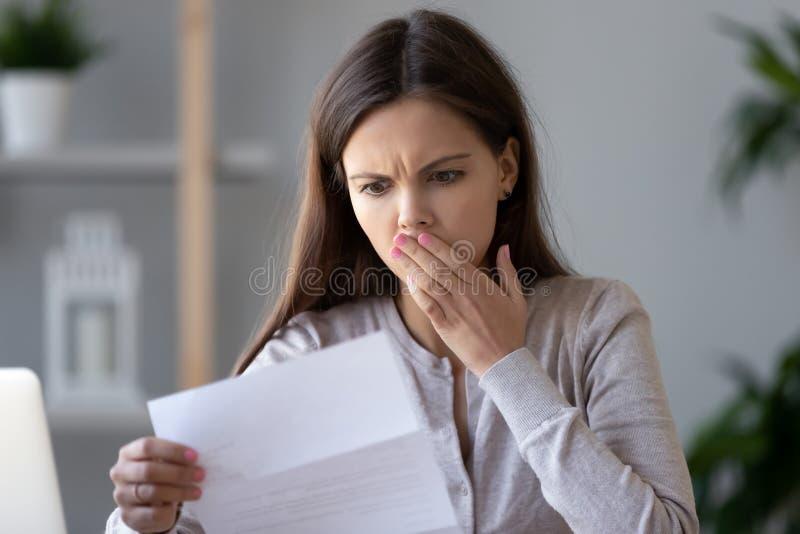 Shocked усилил письмо документа чтения молодой женщины о задолженности стоковые фото