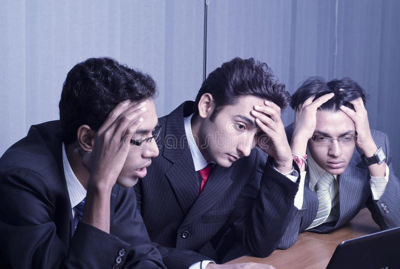 Shocked. 3 professionals are looking at laptop in shocked state stock photography
