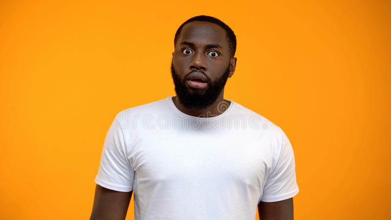 Shocked African-American man looking at camera isolated on yellow background. Stock photo stock images
