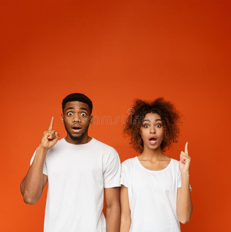 Shocked african-american man and woman pointing fingers upwards. Unbelievable sale. Shocked african-american man and woman pointing fingers upwards at free space royalty free stock photography