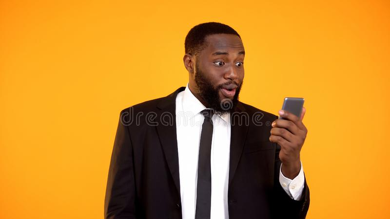 Shocked afro-american man in business suit holding phone, receiving mail, news. Stock photo royalty free stock images