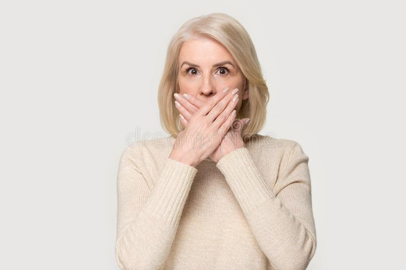 Shocked aged female covering mouth with hands feel scared stock photos