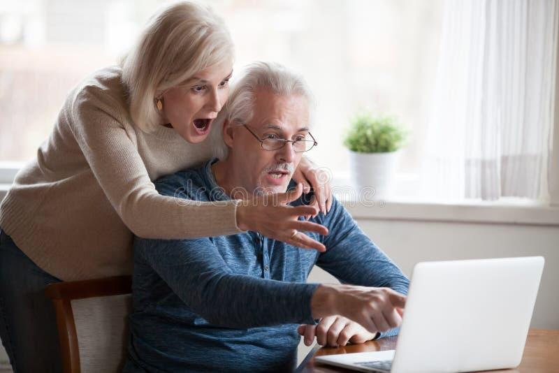 Shocked alterte die Paare, die online durch Nachrichten am Laptop überrascht waren stockfoto