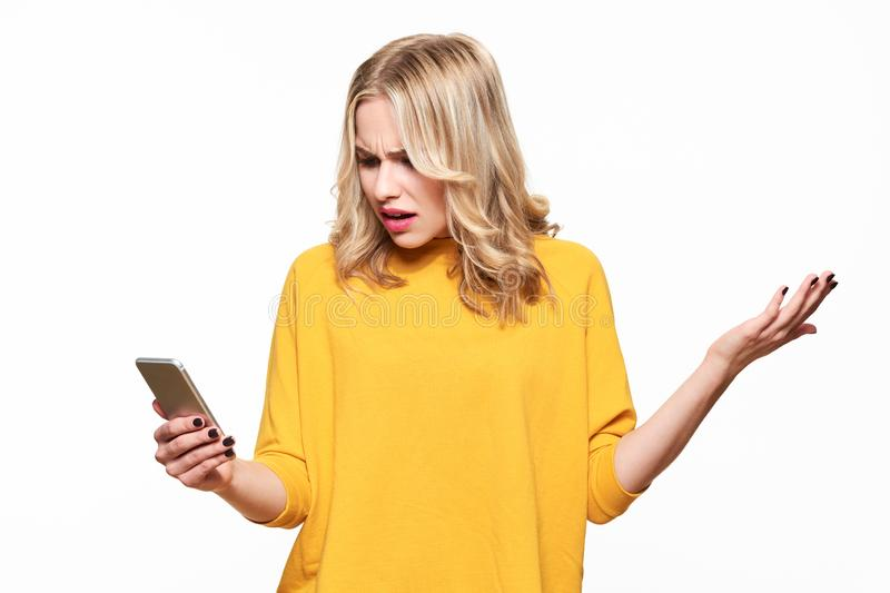 Shocked angry young woman looking at her mobile phone in disbelief. Woman staring at shocking text message on her phone. Shocked angry young woman looking at stock image