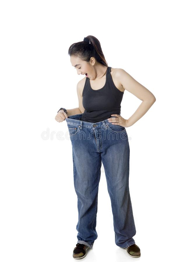 Shocked Arabian woman trying her old jeans royalty free stock photo