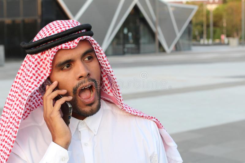 Shocked Arabic man calling by phone royalty free stock photo
