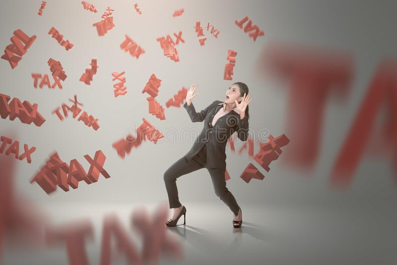 Shocked asian business woman with falling tax sign around her royalty free stock image