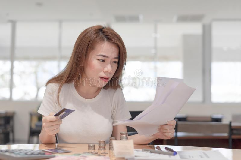 Shocked asian business woman holding credit card sitting on desk looking at bills payment in office background royalty free stock photos