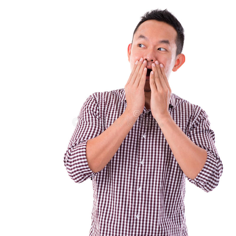 Shocked Asian man. Covering his mouth by hand, isolated on white background. Asian male model stock photo