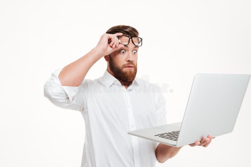 Shocked astonished man in eyeglasses looking at laptop screen royalty free stock image