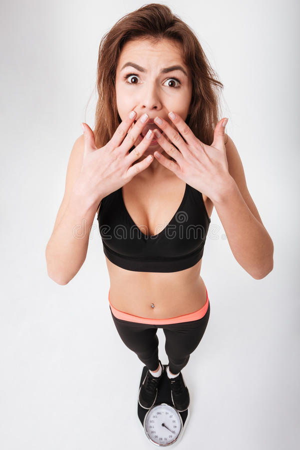 Shocked astonished young fitness woman standing on weighting scale. Over white background royalty free stock photos