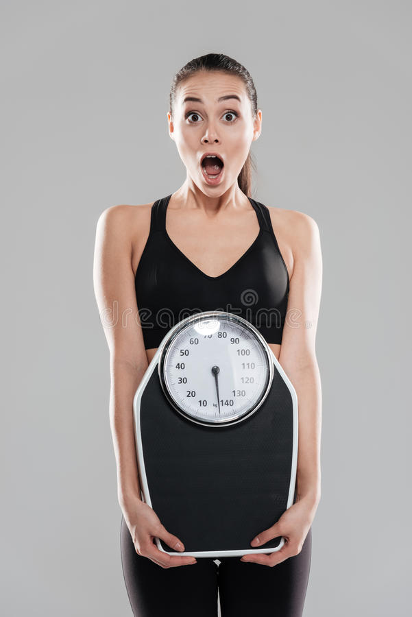Shocked astonished young woman athlete holding weighing scale. Over gray background royalty free stock image