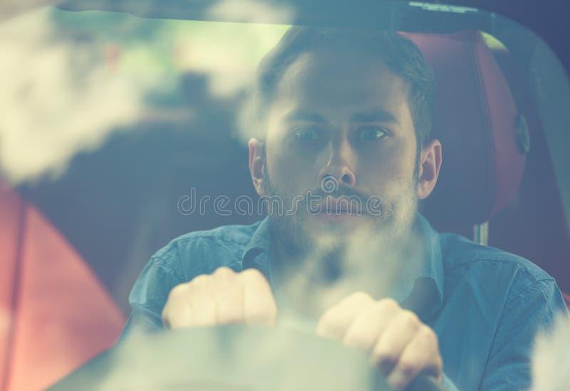 Shocked asustó al conductor joven de mirada divertido en el coche fotos de archivo