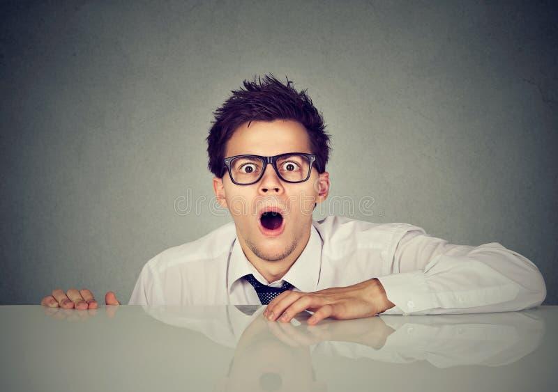 Shocked asustó al hombre joven que salía de debajo la tabla foto de archivo libre de regalías