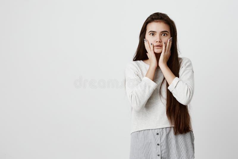 Shocked aturdiu a menina moreno emocional mantém as mãos em mordentes, sendo incomodado para escutar conselhos de seus pais europ fotografia de stock