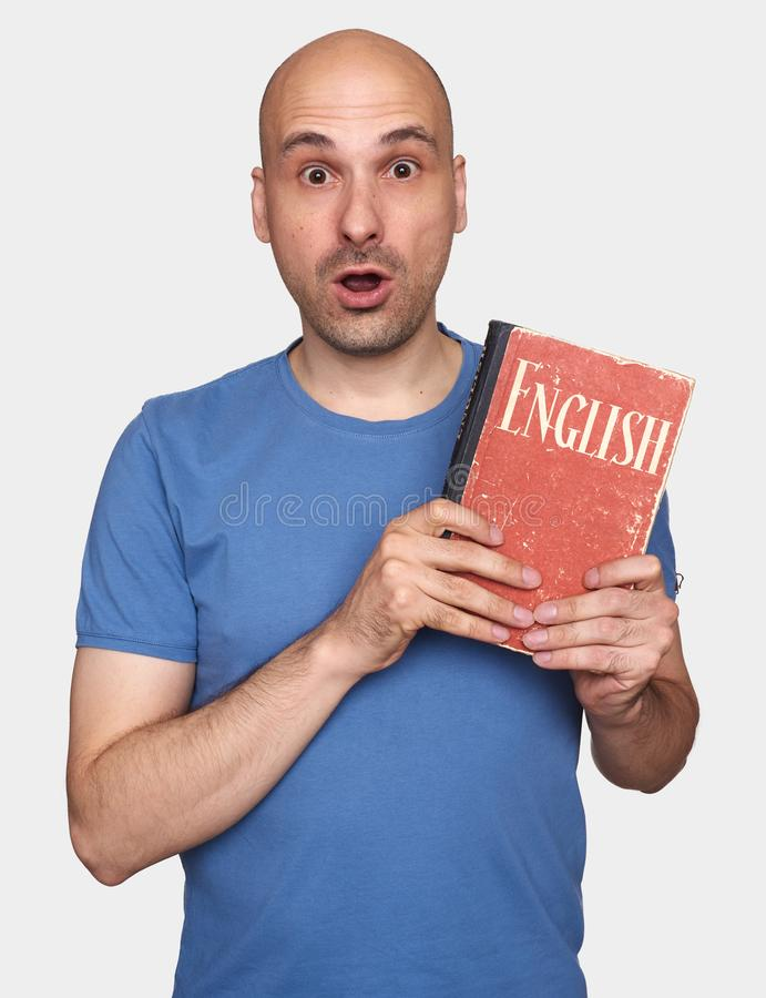 Shocked bald man holds an English textbook royalty free stock images