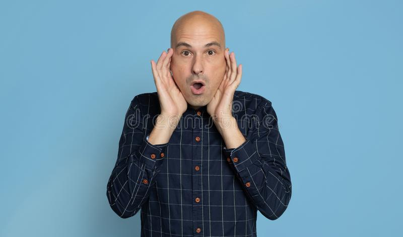 Shocked bald man isolated over blue royalty free stock photo