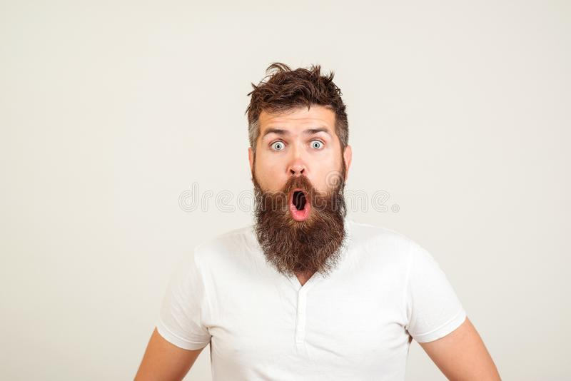 Shocked bearded man stares at camera. Bearded hipster guy widely opened mouth and eyes. Human face expressions and emotions. Wow!. Surprised young man on white stock photo