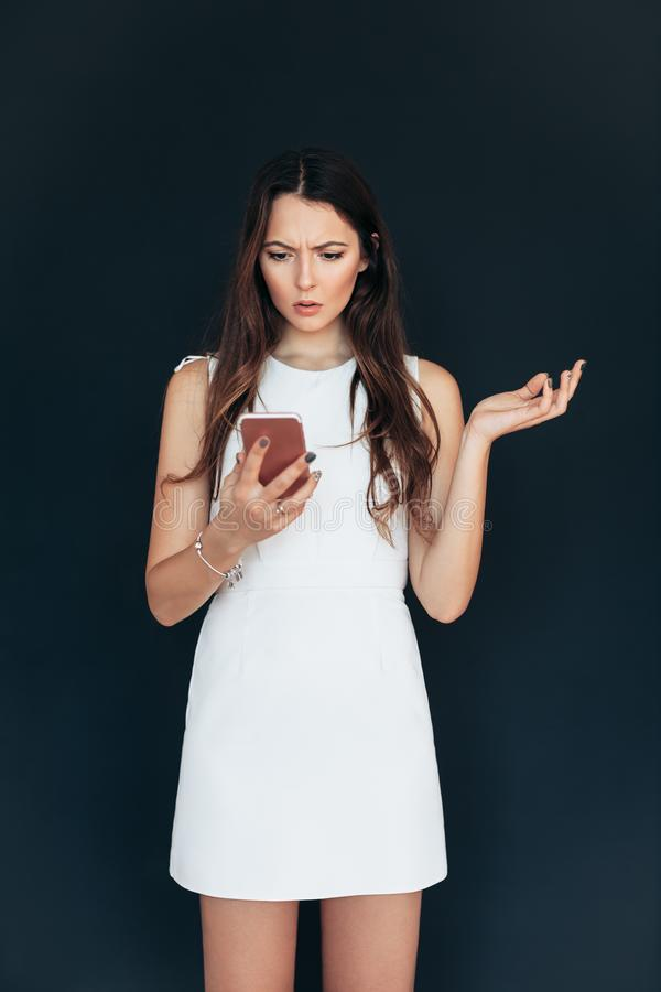 Shocked beautiful woman looking at smartphone. Upset and disappointment emotion stock image