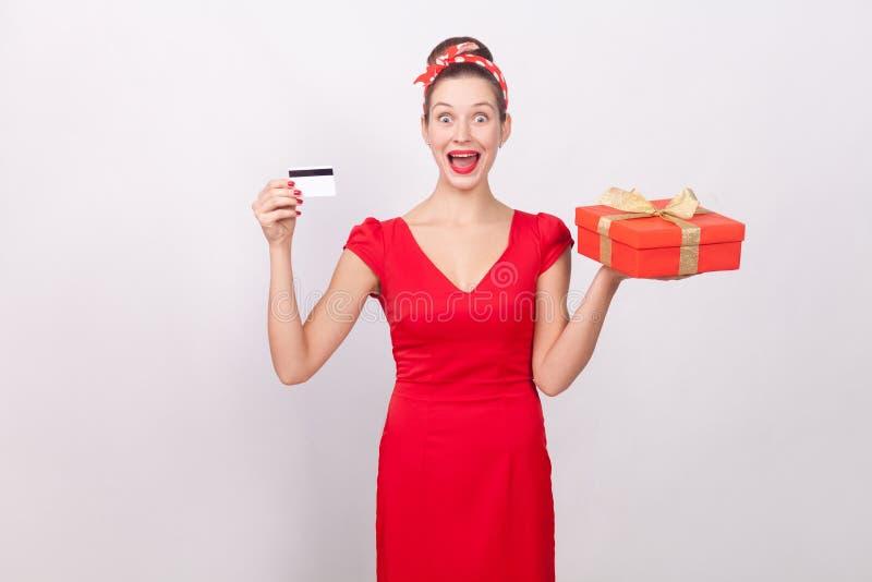 Shocked beautiful wonder woman, holding credit card, gift box. stock photos