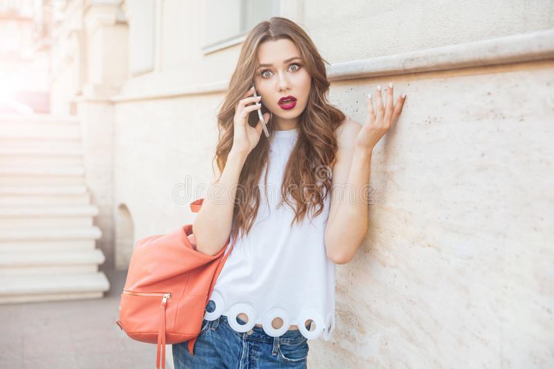 Shocked beautiful young woman holding her smartphone outdoors royalty free stock photo