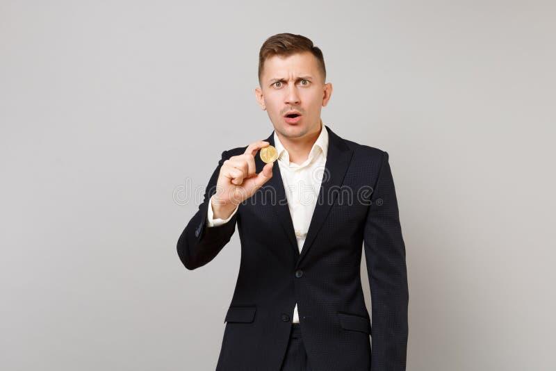 Shocked betraf jungen Geschäftsmann im klassischen schwarzen Anzug und im Hemd, die das bitcoin hält, zukünftige Währung lokalisi lizenzfreie stockbilder