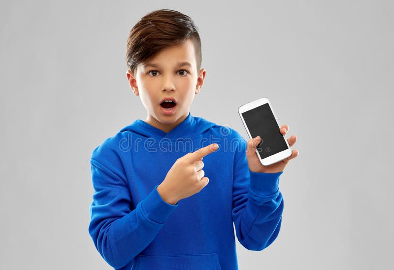 Shocked boy in blue hoodie showing smartphone. Childhood, technology and people concept - shocked boy in blue hoodie showing smartphone with blank screen over stock image