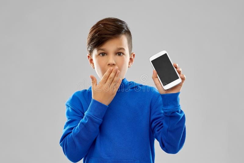 Shocked boy in blue hoodie showing smartphone. Childhood, technology and people concept - shocked boy in blue hoodie showing smartphone with blank screen over stock photography