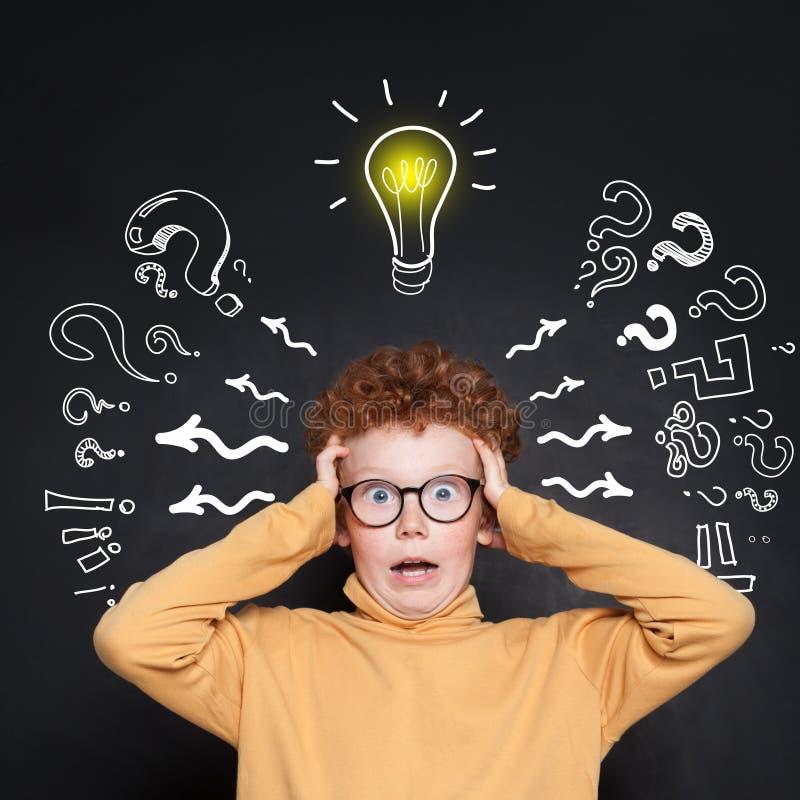 Shocked boy student with lightbulb on black background stock photos