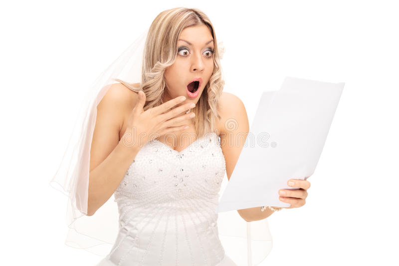 Shocked bride looking at a bill stock image