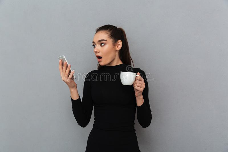 Shocked brunette woman in black clothes looking at smartphone. While holding cup of coffee over gray background stock photography