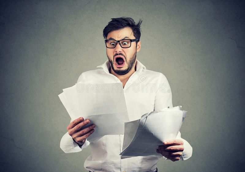 Shocked business man looking through papers with bills. Young shocked guy in glasses looking at papers bank documents with list of bills and fees and feeling royalty free stock images