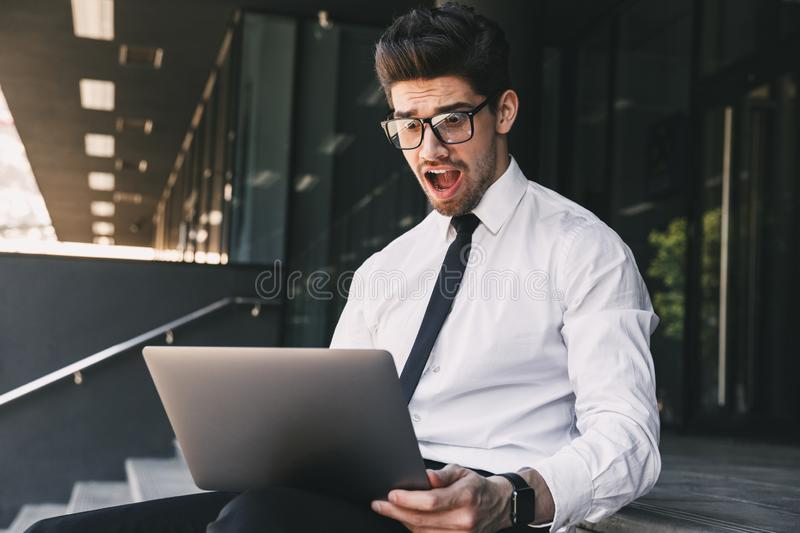 Shocked business man near business center using laptop computer. Image of handsome shocked business man near business center using laptop computer stock images