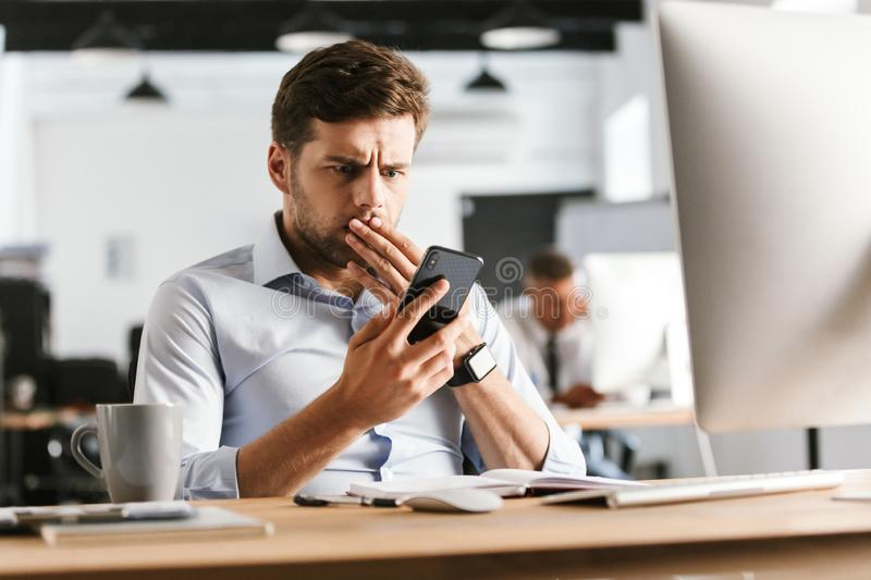 Shocked business man using smartphone and covering his mouth. While sitting by the table in office royalty free stock image