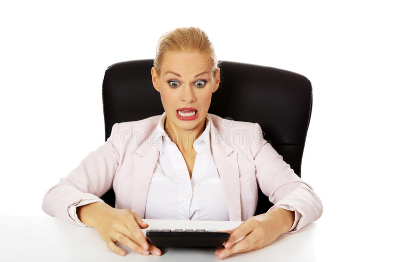 Shocked business woman sitting behind the desk with calculator stock photo