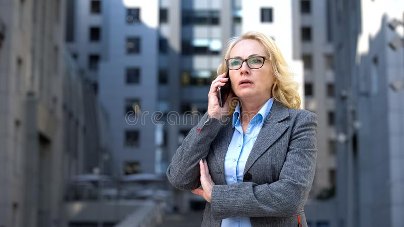 Shocked business woman talking phone outdoors office, bad news, work failure royalty free stock images