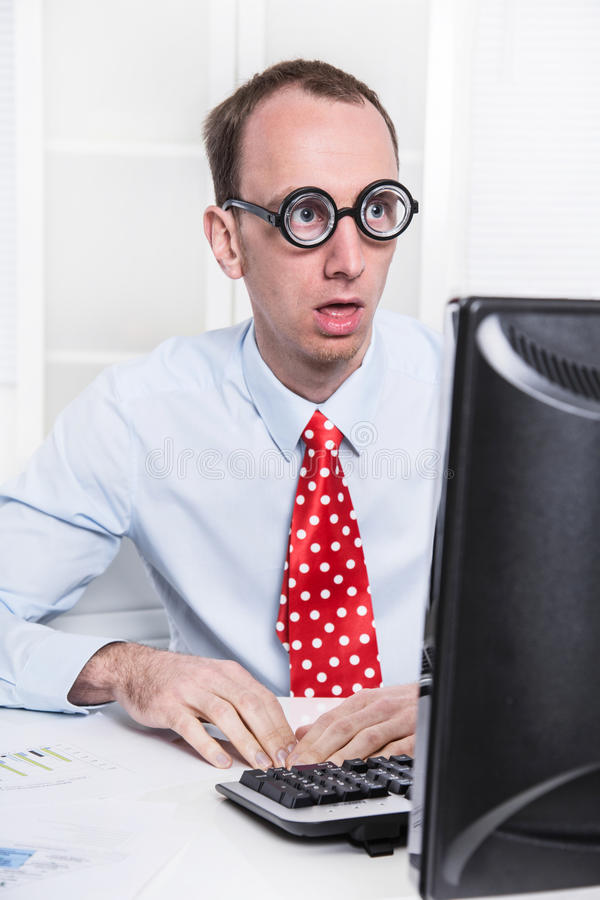 Shocked businessman at desk staring at computer and can't believ royalty free stock photography