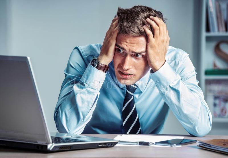Shocked businessman dissatisfied his earnings, looking at laptop. royalty free stock photos