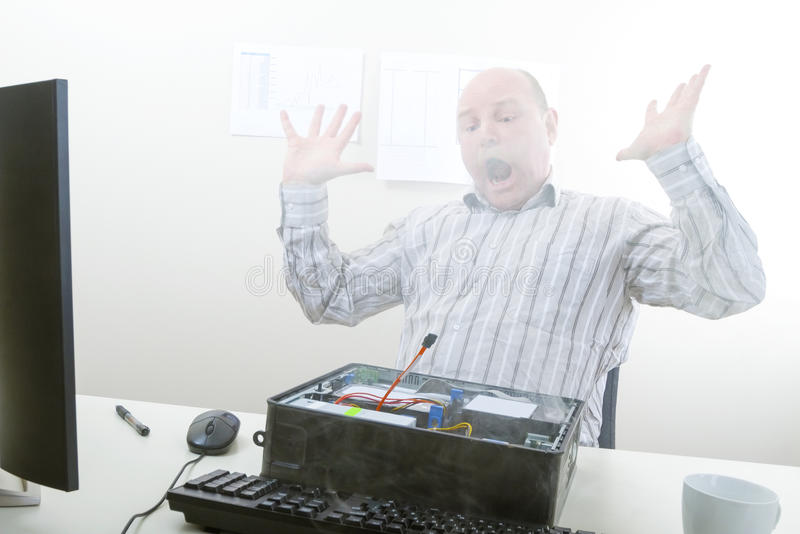 Shocked Businessman Looking At Smoke Emerging From Computer royalty free stock image