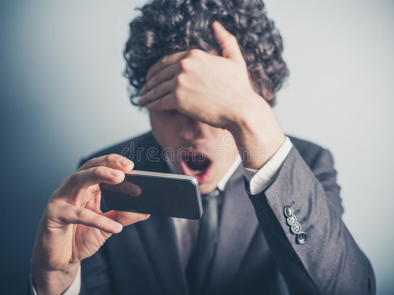 Shocked businessman reading on his smartphone stock images