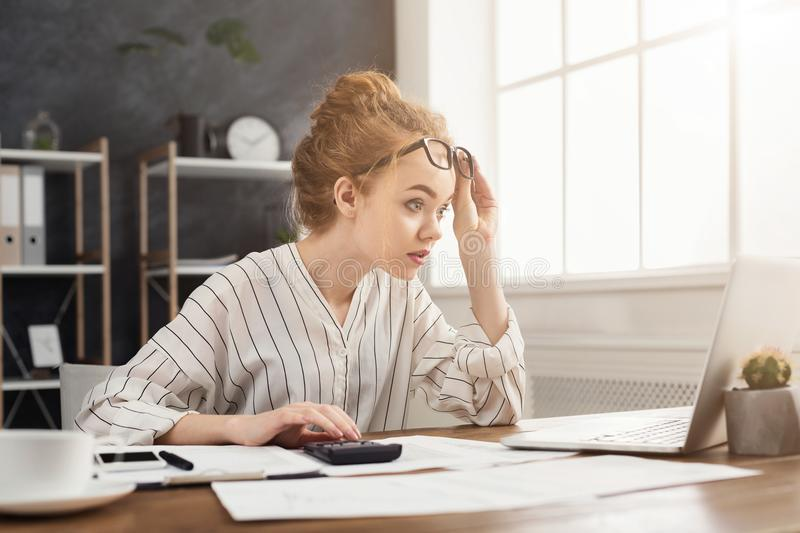 Businesswoman amazed by reading breaking news on laptop royalty free stock images