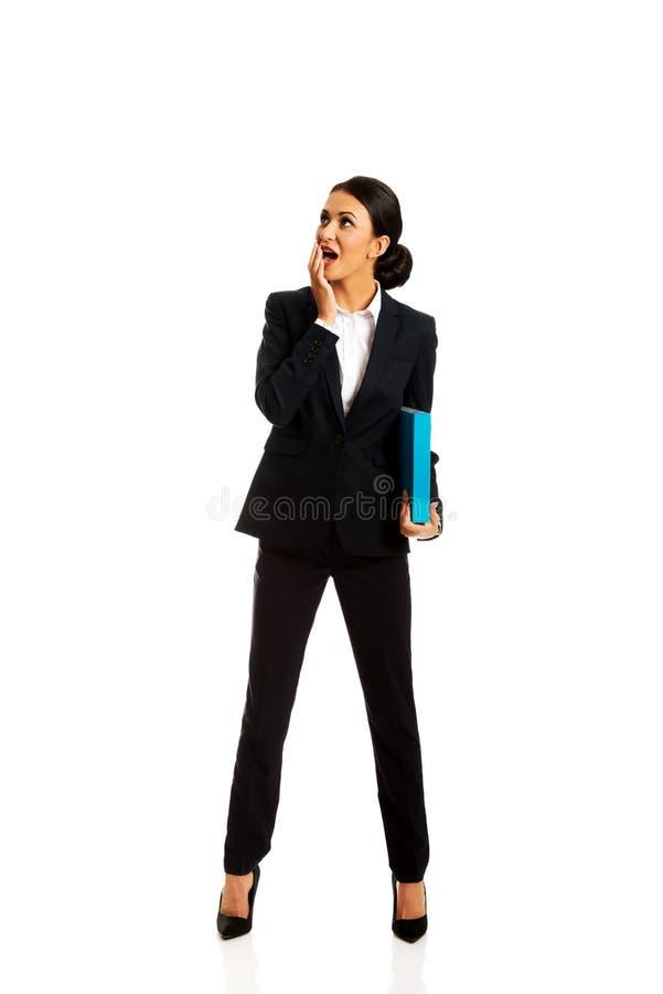Shocked businesswoman holding a binder stock photo